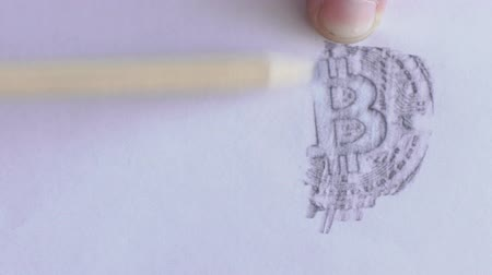 ołówek : Young male professional is drawing bitcoin image on white paper using pencil, on table in trader company, person depicts symbol of peering payment system on sheet on desk in room with daylight. Wideo