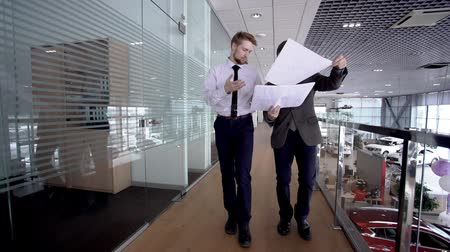 move well : Two young businessmen looking to the reports while walking through the gallery in autocenter. slow motion.