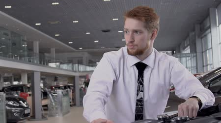car dealership : In showroom red-haired bearded consultant man in white shirt talks about advantages of an expensive vehicle purchase with discount on store. slow motion.