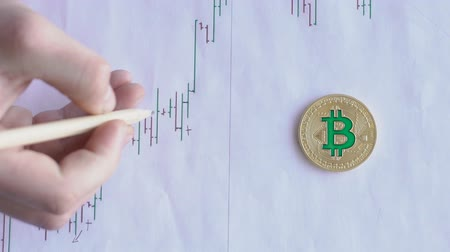 usado : Hand with help of pencil makes marks on chart on sheet with gold bitcoin on desktop. Close-up.