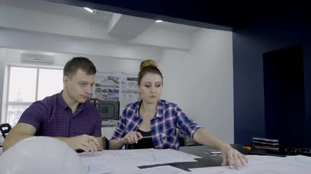 архитектурный : Male and female engineers are working on the building blueprint together in their office. Architects are sitting at the table with helmet and papers on and correcting the scheme according to seismology research results using pencils and ruler.