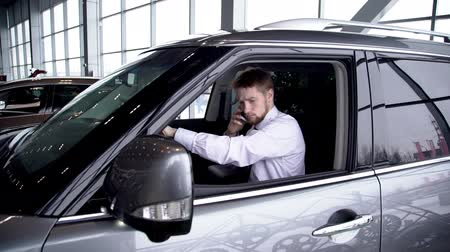 car rental : Young handsome businessman using smartphone, sitting in new automobile in car center, bearded man testing transport, examining, touching, holding phone. Concept: buying, purchasing, office interior.