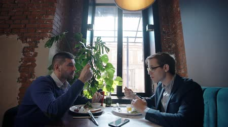 oposto : Two young friends are eating food, talking, sitting at table in restaurant, businesspeople are at business lunch, discuss work, enjoying delicious meal. Partners having time on soft sofa in room with window, brick walls. Concept: meeting, good mood, profe Stock Footage