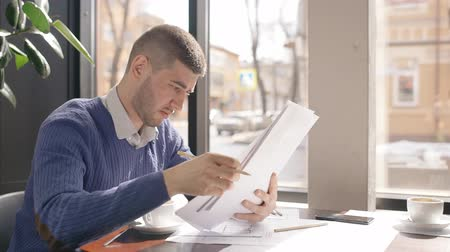 bankier : Young male employee is in working process with contract, sitting at table in cafe, businessman is holding, reading documents on background window, papers and telephone is on desk. Business person wears business style clothes. Concept: paperwork, modern in Wideo