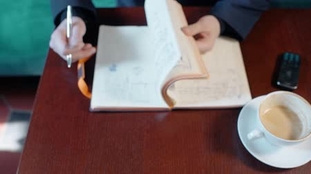 seriously : Young businessman is working with notebook, sitting at table in cafe interior. Man works during coffee break, thumbs through pages of diary, reads notes. Guy has nice day on soft sofa, drink and phone is on wooden desk. Concept: thinking person, lifestyle Stock Footage