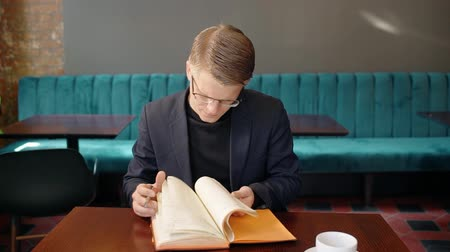 telefonkönyv : Portrait of businessman checking his meeting schedule in notebook in the cafe. Concept of: business people, cafe interior, notebook paper, reading glasses,
