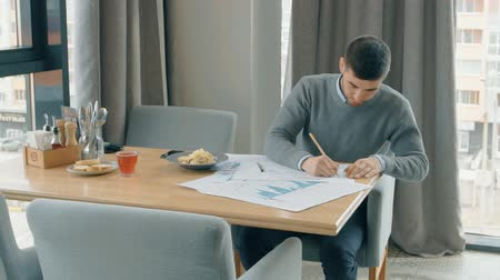 yetenekli : Young man is working on blueprint, sitting at table in cafe interior, professional draws on drawings, dish on desk by window with city view. Concept: new project, business person, graphic job. Stok Video
