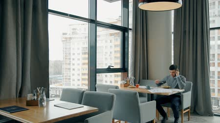 żyrandol : Successful businessman is talking on phone during business lunch at cafe table, young man makes call, enjoys delicious dish at desk by panoramic windows. Concept: good dinner, entrepreneurship, communication. Wideo