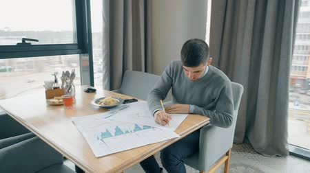 cuidadoso : Young businessman is working with financial documents, sitting at cafe table, man thinks, analyzes, writes on papers with graphs, diagrams near window. Concept: business strategy, solutions, investment.
