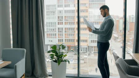 white out : Portrait of businesman reading report near the window in cafe. Concept of: business peope, cafe interior, financial planning, paper work, city view, sussessful people. Stock Footage