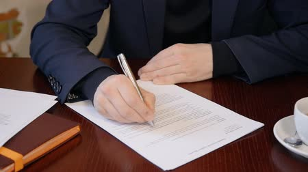 holding newspaper : Close up of businessman corrcting the document with pen in his office. Concept of: business people, contract signing, documents on desk, ball pen, office table