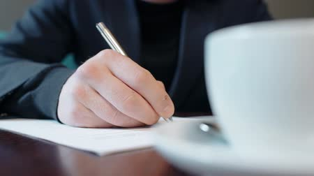 papelada : Close up hand of businessman signing contract with silver ballpen on the table with cup of coffee. Concept of: business people, contract signing, documents on desk, coffee cup, ball pen