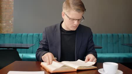 telefonkönyv : Portrait of businessman turning over the pages of his notebook in cafe. Concept of: business people, cafe interior, notebook paper, reading glasses, coffee cup, turning over pages.