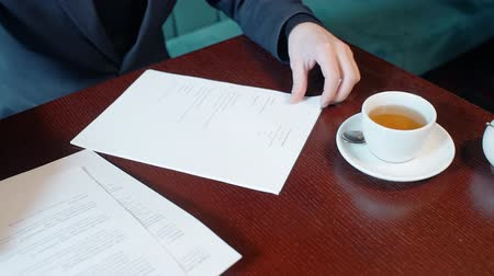 holding document : Hands of businessman reading contract in the cafe. Concept of: business people, documents on desk, tea cup, cafe table, ball pen.