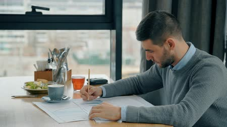 concentrar : Young bearded man is writing on papers at table in coffee shop, businessman working on new project, sitting at desk with meal near window. Concept: entrepreneurship, financial specialist, doing paperwork.