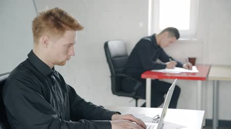 stříbřitý : Young guy is working with laptop sitting in workplace in modern office, employee doing work, looking at screen, typing, colleague is writing beside. Concept: technology, professional staff, workspace. Dostupné videozáznamy