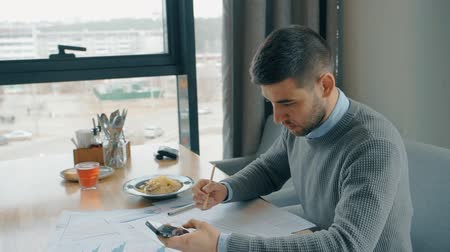 currency trading : Portrait of handsome businessman calculation on his smartphone and checking paper graphs in cafe. Concept of: business peope, cafe table, modern interior, charts and graphs, financial planning, delicious food, paper work, smartphone hand, city view.