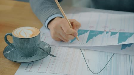 franczyza : Young man is writing on papers with diagrams at table in coffee shop, businessman working with financial project, sitting at desk with cup cappuccino. Concept: commercial, paperwork, professional. Wideo