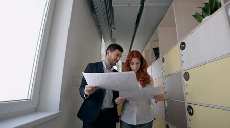 redhead suit : Young businessman and woman are talking about project, walking in large company, busy colleagues discussing documents, brainstorming, smiling, going in modern office space. Concept: collaborating, partnership, corporate.