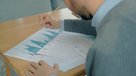 currency trading : Portrait of handsome businessman drawing tendencies on market situation graph in the cafe. Concept of: business peope, cafe table, charts and graphs, financial planning, delicious food, paper work. Stock Footage