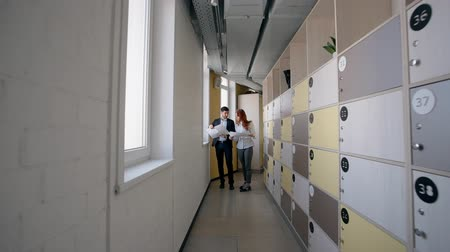 enterprise : Young man and woman discussing investment project standing in corridor of company, business people are holding documents, analyzing, talking in bright room with windows and lockers. Concept: staff, brainstorming, working day.