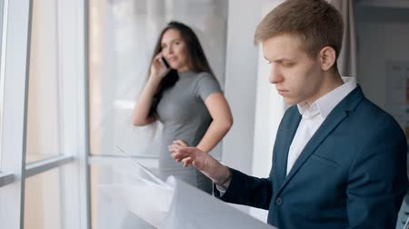 týden : Young successful business people in work process in modern interior of company, businessman is looking at project, woman is talking on phone, standing by window in office. Concept: startup, investment, lifestyle.