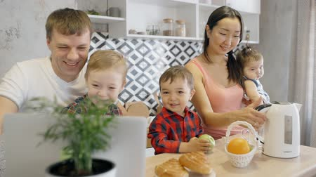 demlik : Multiethnic family enjoying watching cartoons on the laptop, asian mother with baby on the hands putting electric teapot to the counter in the kitchen. Indoors.