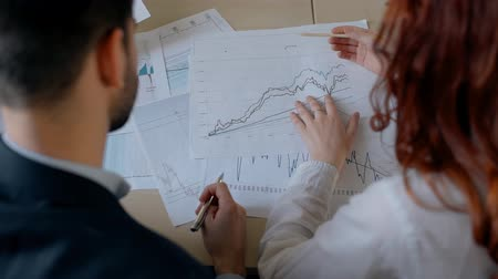 oposto : Businessman in suit and red hair female financial analytic researching market trends on printed graphs in the office. Indoors. Back view. Stock Footage