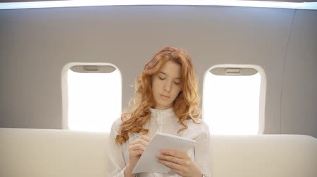 prive jet : Young beautiful businesswoman is writing sitting on couch in airplane interior, red haired female in white shirt is taking notes in notebook, planning day during business trip in private plane. Concept: travelling, flight, lifestyle.