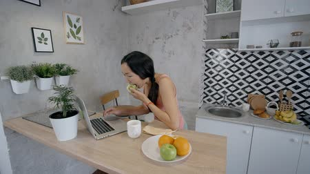 tendo : Beautiful brunette is looking at laptop screen, eating apple sitting in home interior, young woman in casual clothes is using silvery pc, typing in modern kitchen with daylight. Concept: browsing web, technology, fruit breakfast.