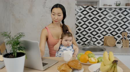 silvery : Young beautiful mom with baby using laptop sitting at table in kitchen, Asian woman and little girl are looking at pc screen, typing at desk with fresh fruits and plant in apartment. Concept: motherhood, working, technology.