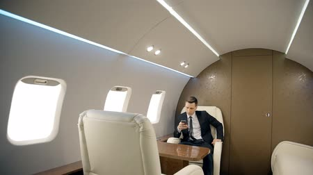 cellulare : Young successful businessman is using smartphone while sitting in private plane, elegant business person in suit with tie is looking at device screen during business trip. Concept: entrepreneurship, technology, flying. Filmati Stock