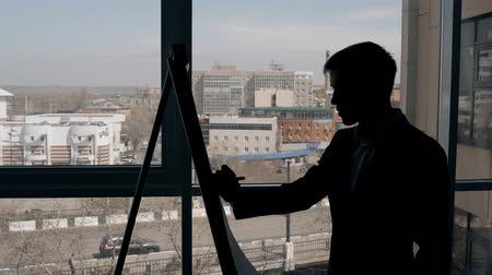 side window : Young businessman is taking notes standing in modern office, handsome entrepreneur in suit is writing on paper board during working day near window with city view. Concept: entrepreneurship, successful person, planning.