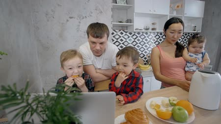 demlik : Multiethnic family enjoying being together in the home kitchen: Father and two sons watching cartoons on the laptop on the counter near plate with fruits and electric teapot and asian mother holding baby. Indoors.