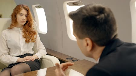 redhead suit : Young successful business couple is talking sitting at table in airplane interior, beautiful businesswoman and elegant businessman are communicating opposite each other in private jet. Concept: business talk, flight, executive. Stock Footage