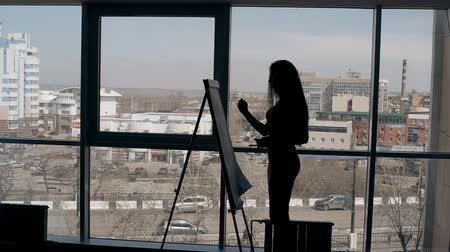 lavagna bianca : Young businesswoman is writing on paperboard, standing at modern office, beautiful female taking notes, planning working day on background of dynamic urban view. Concept: work week, career growth, management.