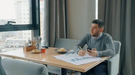 semana : Young male professional working with project, holding smartphone, sitting in cafe, attractive businessman is writing, using phone in paper work at table with dinner in modern interior. Concept: technology, service, connection. Stock Footage