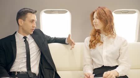 oblek : Male and female lawers talking in private jet. Man in suit and woman with red hair having business trip. Professionals sitting on the withe leather sofa and discussing their strategy.