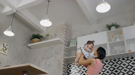 dát : Young asian mother playing with her baby in the kitchen. Woman in pink t-shirt standing in modern interior, holding her daughter in the hands, above the head, throwing her up, catching and kissing. Dostupné videozáznamy