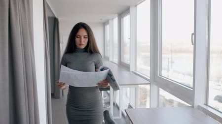 panoya : Young businesswoman saleswoman reading financial report going throught bright corridor. Woman in grey dress holding printed document in her hand in the office with big window. Portrait. Slow motion.