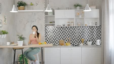 concentrando : Young asian businesswoman working on laptop at home. Woman sitting at the counter in the kitchen with stylish interior, drinking coffee and using her brand-new laptop for remote job. Portrait.