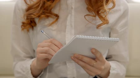ügyvéd : Young curly lawyer businesswoman is making notes in notebook sitting in airplane interior, red haired chief female employee is writing down ideas in working process during business voyage in airliner. Concept: travelling, working, flight.
