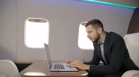 his : Portrait of young financial analyitc worling on laptop in private jet. Concept of: entrepreneur, lawyer, business people, plane flying, laptop working. Stock Footage