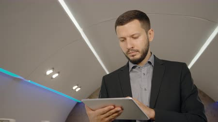 týden : Young bearded lawyer businessman in working process, using tablet in personal airplane, entrepreneur handsome man holding device, looking, touching screen, standing in plane interior. Concept: business travel, aircraft, flight. Dostupné videozáznamy