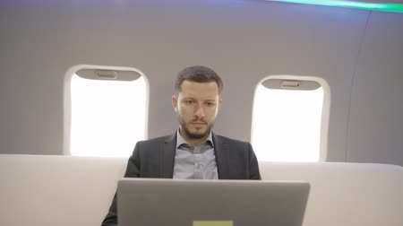 gentleman : Young cheerful lawyer businessman working with laptop, having fun in airplane interior, stylish entrepreneur is enjoying profitable deal during flight in first class. Concept: flying, good mood, entrepreneurship.