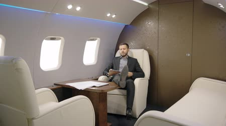 advokát : Portrait of lawyer succesful man taking a seat in his private plane and entrepreneur reading news on his tablet. Concept of: business people, plane flying, tablet reading.