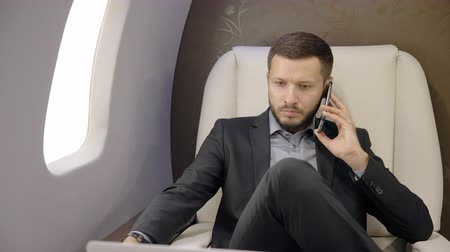 important : Young businessman lawyer talking on phone, using tablet in airplane interior, bearded entrepreneur man making important call, looking at device screen, sitting in leather chair in airliner. Concept: successful person, traveler, professional. Stock Footage