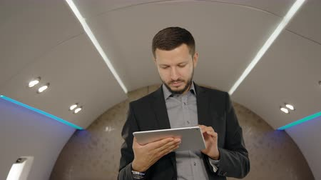 legfőbb : Portrait of chief banker director man standing in plane and lookins to the screen of his tablet. Concept of: business people, plane flying, tablet reading.