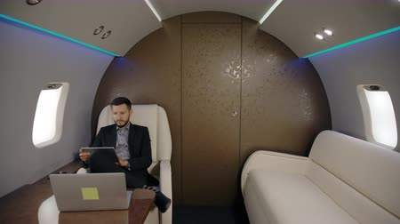 cabins : Portrait of successful investor expert analyst young man working on laptop in private jet. Concept of: business people, plane flying, laptop working.