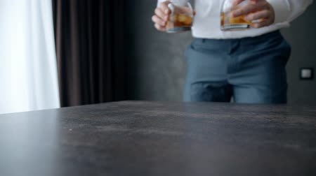 preocupações : Man dressed in formal blue suit put two small glasses with alcohol on wooden lacquered table. Whiskey with ice freshes and make relax, forgot about all problems and worries. It is standing and waiting you.